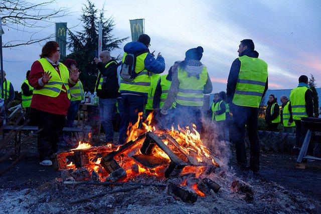 Gilets Jaunes - Yellow Jackets Standing Near A Bonfire.
