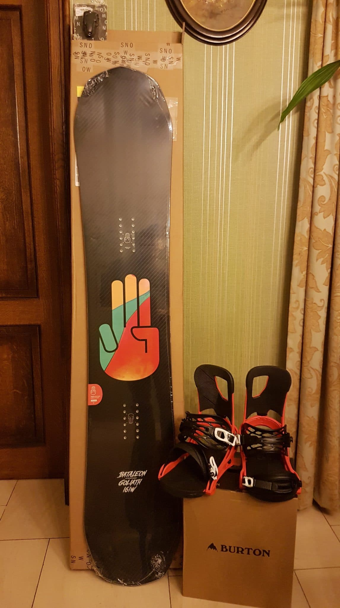 Photo of the Bataleon Goliath 161W snowboard and a pair of red Burton Cartel bindings
