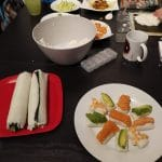 Table Filled With Ingredients And Already Rolled Sushi Rice